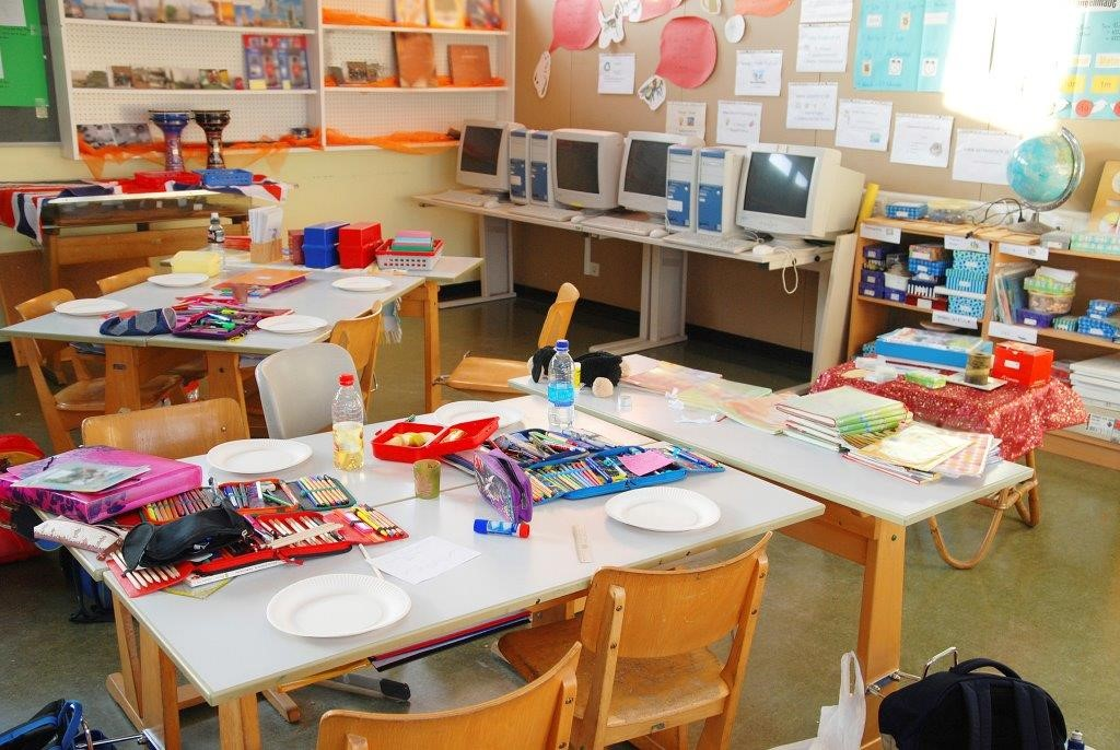 A very messy, but colorful, classroom with art supplies on tables.  Artwork and projects are posted on the walls.  Lots of books are available for reading.  A globe sits next to a row of computers.