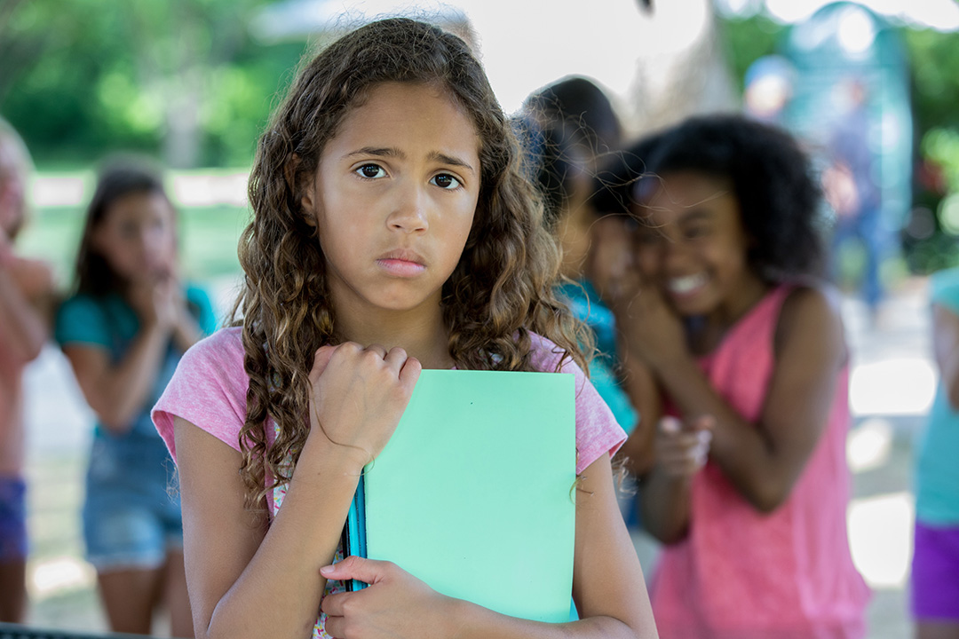 girl looks stressed and sad while kids in background snicker