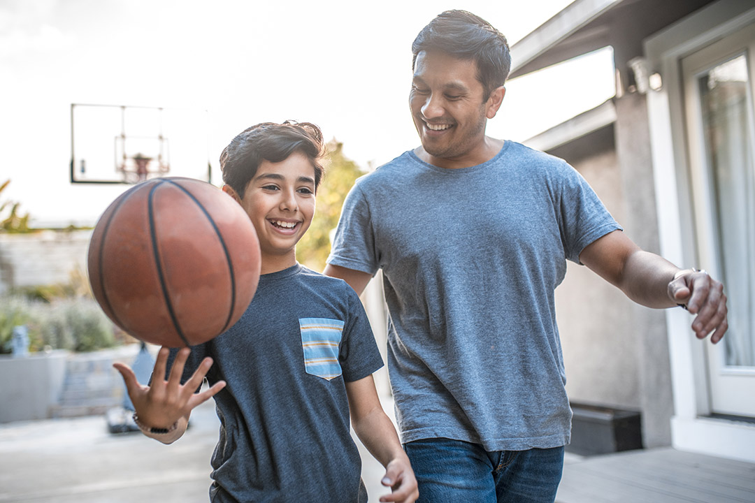 A father and son plays basketball in their home driveway