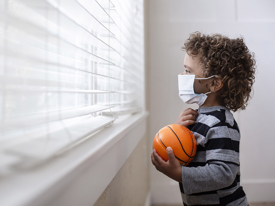 a young child with a PPE mask looks out the window