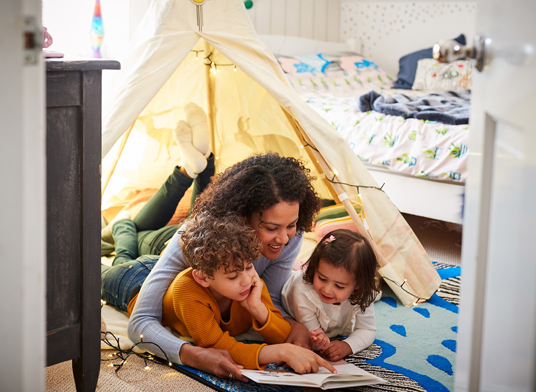A mother sits in a small tent with her children while reading a book inside their bedroom