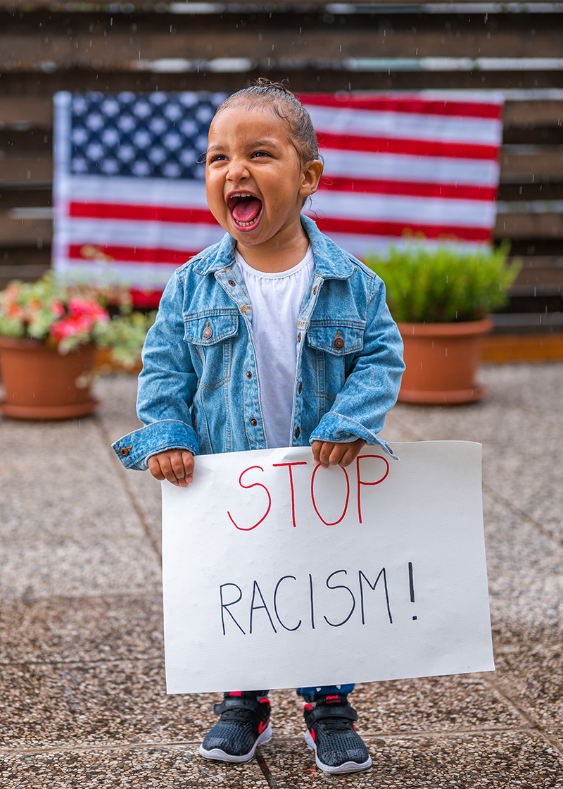 Gleeful toddler holds 'stop racism!' sign with U.S.A. flag in background