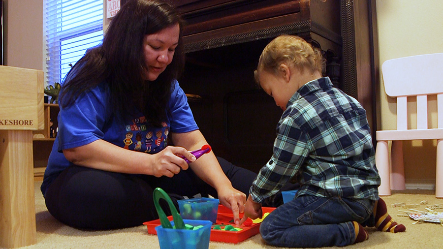 A care giver engages with a toddler with toys practicing cause and effect and joint attention