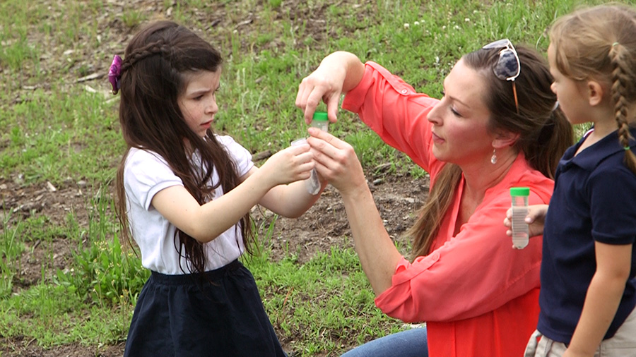 A care giver conducts a science project with children using water specimen tubes outdoors