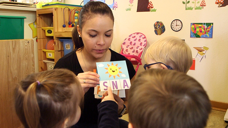 A care giver uses cards with images and letters to practice spelling and literacy