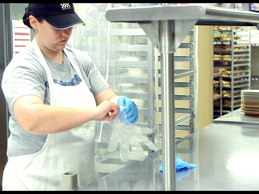 A food service employee puts on disposable gloves for a food task