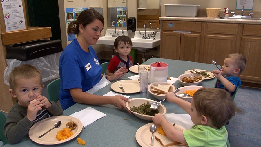children partake in a family style dinner with their caregiver