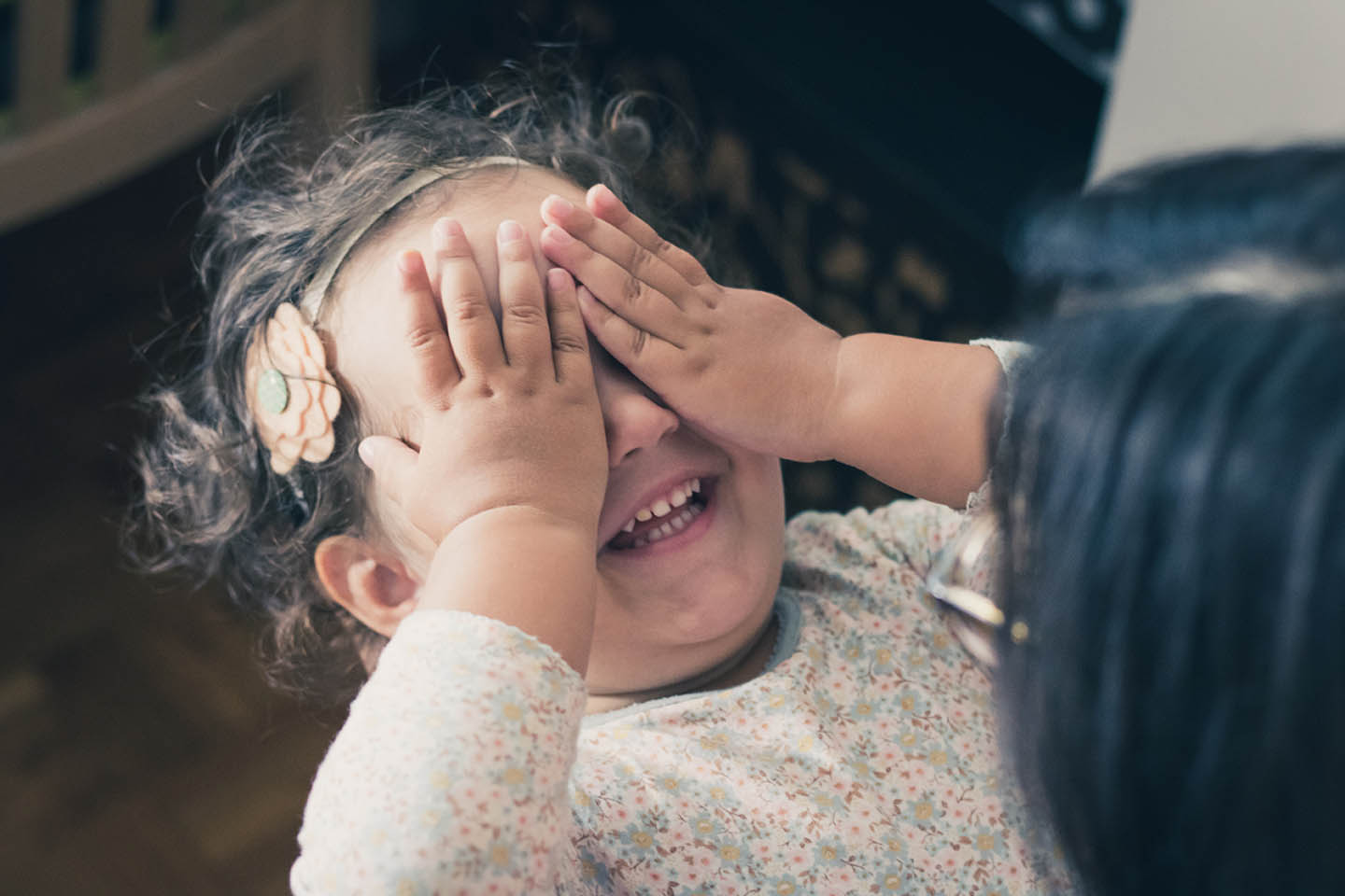 a child covers her eyes to play peek-a-boo